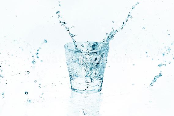 青色に着色されたロックグラスと水が散布する写真・フォト素材