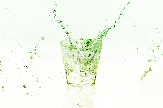 緑色に着色されたロックグラスと水が散布する写真・フォト素材データ