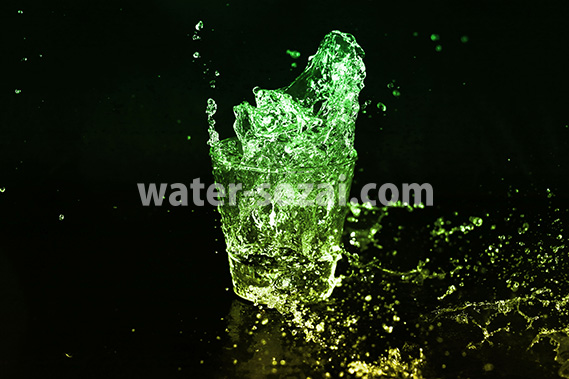 緑色に着色されたロックグラスの水が弾ける写真・フォト素材