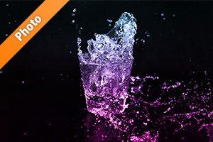 青からピンク色に着色されたロックグラスの水が弾ける写真・フォト
