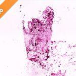 白背景のピンク色に着色されたロックグラスの水が弾ける写真・フォト素材