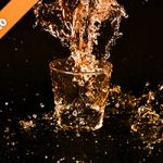 オレンジ色に着色されたのロックグラスと水が散布する写真・フォト素材