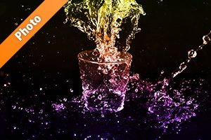 カラフルに着色されたのロックグラスと水が散布する写真・フォト素材