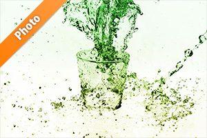 緑に着色されたのロックグラスと水が散布する写真・フォト素材
