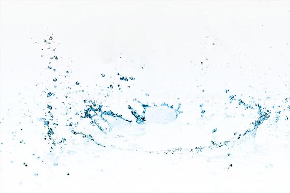 青に着色された水が弾ける写真・フォト素材
