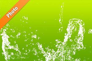 緑背景の水が弾ける写真・フォト