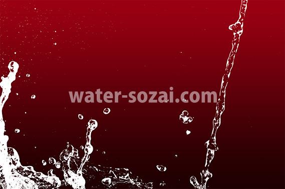 ワインレッド色背景の水が流れ弾ける写真