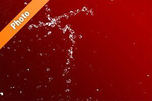 赤い背景の水が跳ねる写真・フォト