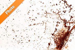 赤茶に着色された水が弾ける写真・フォト