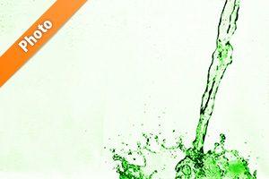 緑色に着色された水が注がれ弾ける写真・フォト
