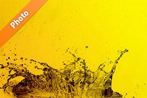 黄色背景の水が弾ける写真・フォト
