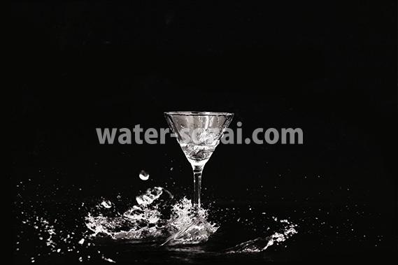 カクテルグラスの下で水が弾ける写真・フォト