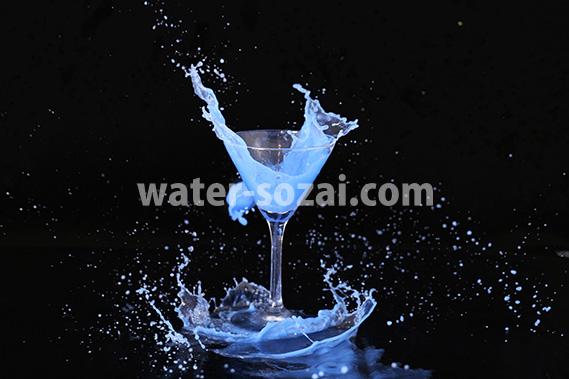 カクテルグラスと青い液体が弾ける写真・フォト素材