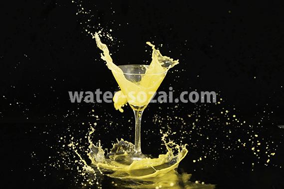 カクテルグラスと黄色い液体が弾ける写真・フォト素材