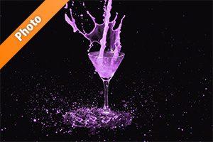 カクテルグラスの上で紫色の液体が跳ねる写真・フォト素材