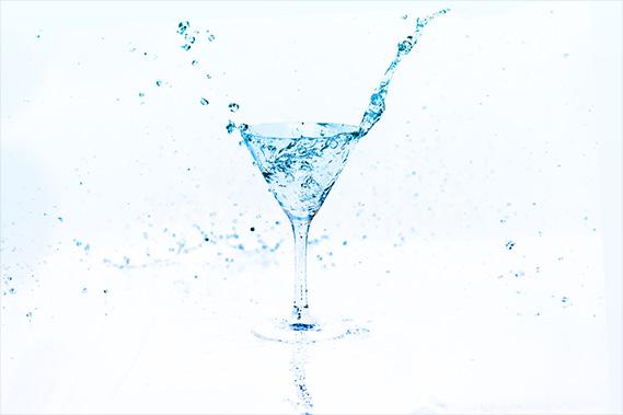 青く透き通るカクテルグラスと水が弾ける写真・フォト素材