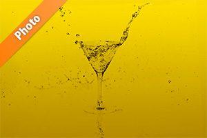 黄色の背景のカクテルグラスと水が弾ける写真・フォト