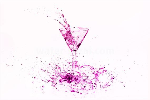 ピンク色に着色されたカクテルグラスと水が飛び散る写真・フォト素材