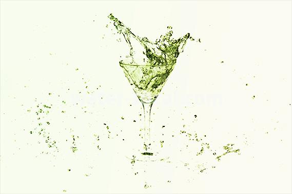 ライムのような色合いのカクテルグラスと水が飛び散る写真・フォト素材