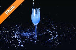 シャンパングラスと青い液体が飛び散る写真・フォト素材