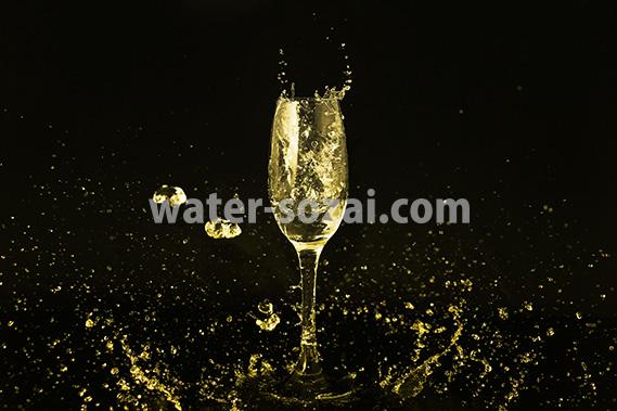 シャンパングラスとゴールドカラーの液体が散布する写真・フォト素材
