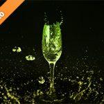シャンパングラスと黄緑の液体が散布する写真・フォト素材