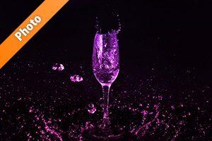 シャンパングラスとピンク・紫の液体が散布する写真・フォト素材