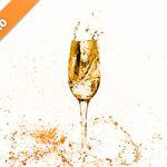 オレンジ色に着色されたシャンパングラスと水が散布する写真・フォト