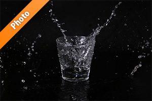 ロックグラスと水が散布する写真・フォト素材