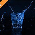 青く着色されたロックグラスと水が散布する写真・フォト素材