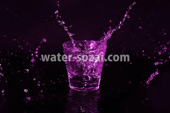 紫色に着色されたロックグラスと水が散布する写真・フォト素材