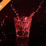 赤色に着色されたロックグラスと水が散布する写真・フォト素材