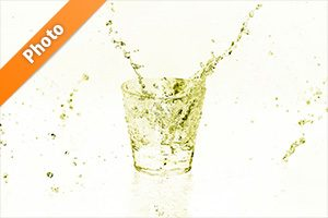 黄色に着色されたロックグラスと水が散布する写真・フォト素材