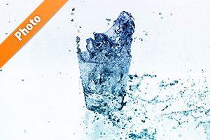 白背景の青色に着色されたロックグラスの水が弾ける写真・フォト素材データ