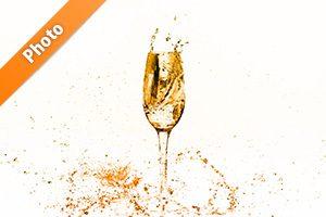 オレンジ色に着色されシャンパングラスと水が散布する写真・フォト