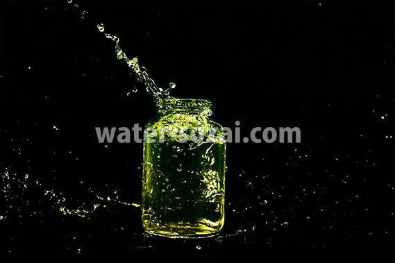 緑色に着色されたビンと水が弾ける写真・フォト素材