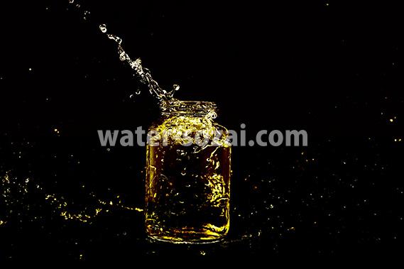 黄色に着色されたビンと水が弾ける写真・フォト素材