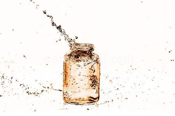 オレンジ色に着色されたビンと水が弾ける写真・フォト素材