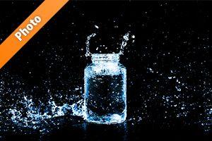青色に着色されたビンと水しぶきの写真・フォト素材