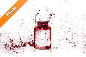 赤色に着色されたビンと水しぶきの写真・フォト素材
