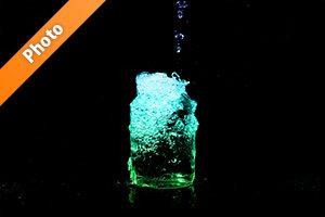 青・緑色に着色されたビンの水があふれる写真・フォト素材