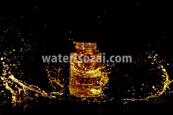 ゴールドカラーに着色されたビンと水が散布する写真・フォト素材