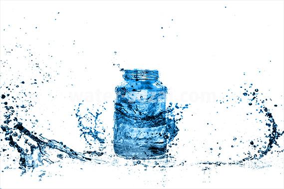 青く着色されたビンと水が散布する写真・フォト素材