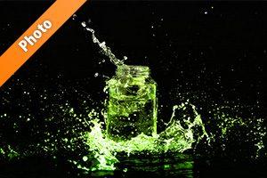 緑に着色されたビンと水が飛び散る写真・フォト素材
