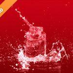 赤い背景のビンと水が飛び散る写真・フォト素材