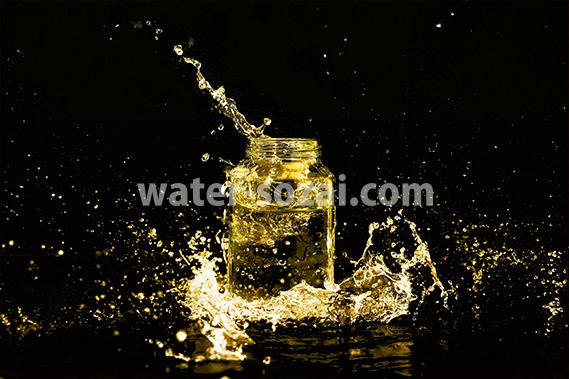 黄色に着色されたビンと水が飛び散る写真・フォト素材