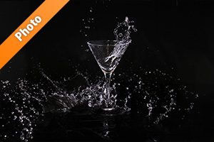 カクテルグラスの水が飛び散る写真・フォト素材