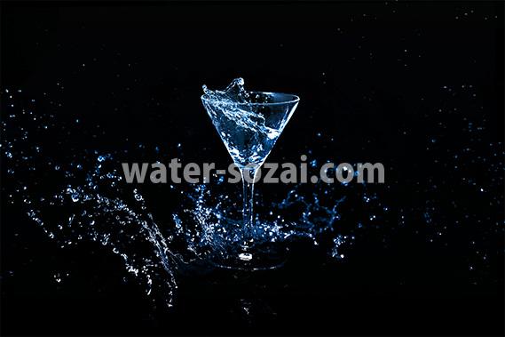 青に着色されたカクテルグラスと躍動する液体の写真・フォト素材