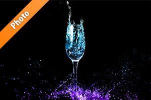 青・紫色に着色されたシャンパングラスと水しぶきの写真・フォト素材
