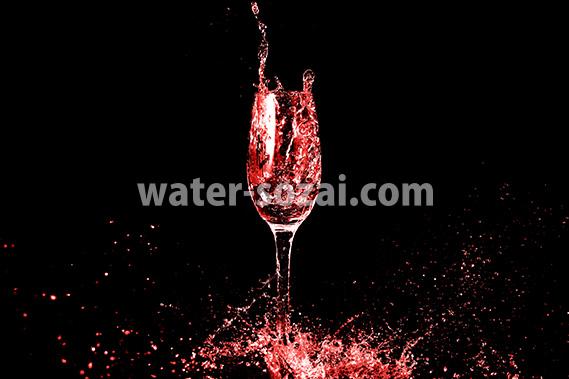 赤く着色されたシャンパングラスと水しぶきの写真・フォト素材
